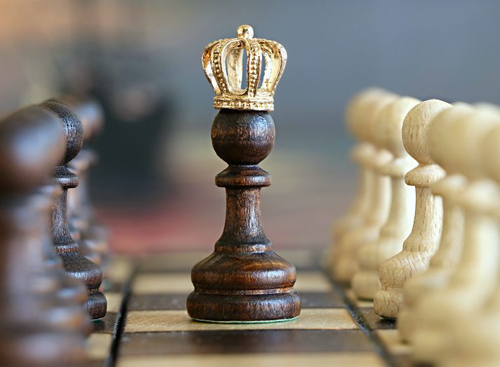 Chess pieces with crown on top of one