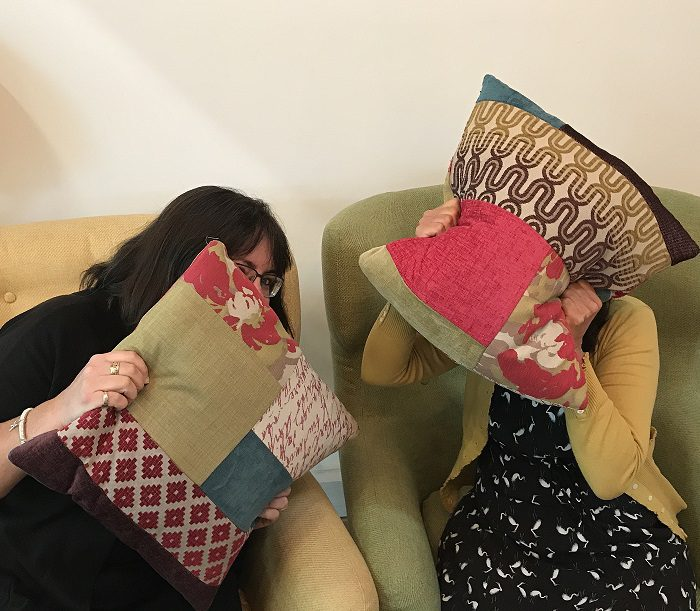 Two people hiding behind cushions